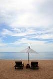 Stuhl und weißer Regenschirm auf dem Strand Stockfotografie