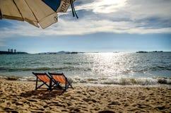 Stuhl und weißer Regenschirm auf dem Strand Lizenzfreies Stockbild