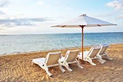 Stuhl vier und Regenschirm am Strand Lizenzfreie Stockfotos