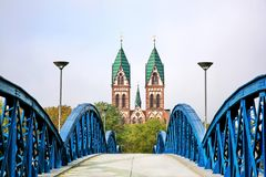 Herz-Jesu Cathedral in Freiburg, Germany. The Stuhlinger bridge leading to Herz-Jesu Cathedral, the gothic cathedral with a high tower in Freiburg, located in royalty free stock photos