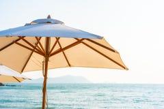 Stuhlregenschirm und -aufenthaltsraum auf dem sch?nen Strandseeozean auf Himmel stockfoto