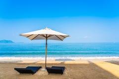 Stuhlregenschirm und -aufenthaltsraum auf dem sch?nen Strandseeozean auf Himmel lizenzfreies stockbild
