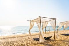 Stuhlregenschirm und -aufenthaltsraum auf dem sch?nen Strandseeozean auf Himmel stockfotografie