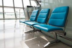 Stuhlreihe im Flughafen Warteraum Stockfotos