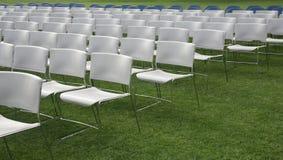 Stuhlreihen und Hintergrund des grünen Grases Lizenzfreie Stockfotografie