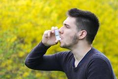 Stuifmeelallergie, jongen die astmainhaleertoestel met behulp van royalty-vrije stock afbeeldingen