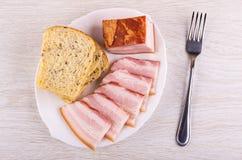 Stuk en plakken van borststuk, brood in schotel, vork op lijst Hoogste mening stock fotografie