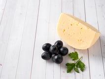 Stuk kaas met peterselie en rode druiven op witte houten achtergrondexemplaarruimte royalty-vrije stock foto