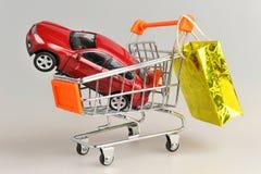 Stuk speelgoed auto in boodschappenwagentje met het hangen van gouden pakket op grijs Stock Fotografie