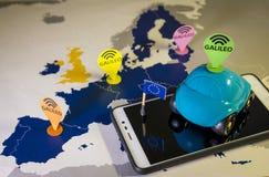 Stuk speelgoed auto, de speld van Galileo en een smartphone over een de EU-kaart Het systeemmetafoor van Galileo royalty-vrije stock foto