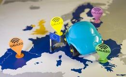 Stuk speelgoed auto, de speld van Galileo en een smartphone over een de EU-kaart Het systeemmetafoor van Galileo royalty-vrije stock afbeeldingen