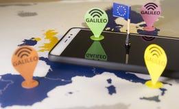 Stuk speelgoed auto, de speld van Galileo en een smartphone over een de EU-kaart Het systeemmetafoor van Galileo stock foto's