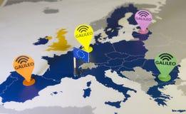 Stuk speelgoed auto, de speld van Galileo en een smartphone over een de EU-kaart Het systeemmetafoor van Galileo stock afbeelding