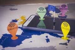 Stuk speelgoed auto en een smartphone over een de EU-kaart Het systeemmetafoor van Galileo stock fotografie