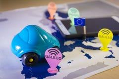 Stuk speelgoed auto en een smartphone over een de EU-kaart Het systeemmetafoor van Galileo stock foto's