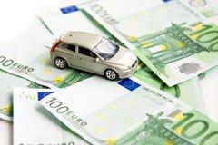 Stuk speelgoed auto en euro op wit stock afbeeldingen