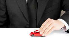 Stuk speelgoed auto en hand van de bedrijfsmens, concept voor verzekering, het kopen, het huren, brandstof of de dienst en reparat Stock Foto