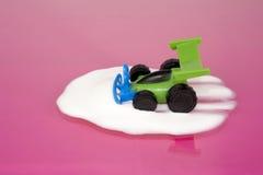 Stuk speelgoed auto het drijven in melk Royalty-vrije Stock Afbeeldingen