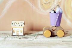 Stuk speelgoed auto, kwartelseieren, een plattelandshuisje met verlichting, op een lichte houten lijst stock afbeeldingen