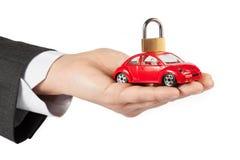 Stuk speelgoed auto met slot op bovenkant in de hand van bedrijfsmensenconcept voor verzekering, het kopen, het huren, brandstof o Stock Foto