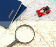 Stuk speelgoed auto met twee paspoorten en vergrootglas op kaart Reis rond de wereld Stock Afbeeldingen