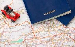 Stuk speelgoed auto met twee paspoorten op de achtergrond van de kaart Royalty-vrije Stock Afbeelding