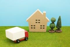 Stuk speelgoed autovrachtwagen en huis op groen gras royalty-vrije stock afbeelding