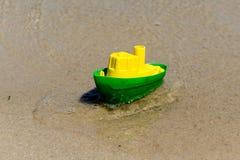 Stuk speelgoed boot in het natte zand van het overzees Op zee de vakantie van de zomer Rondvaarten Royalty-vrije Stock Foto's