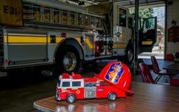Stuk speelgoed brandvrachtwagen en echte brandvrachtwagen Royalty-vrije Stock Foto's