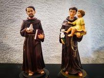 Stuk speelgoed cijfer die van heilige Anthony een jongenskind houden en heilige Francis die een een duifvogel en bijbel houden royalty-vrije stock afbeeldingen