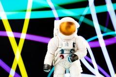 Stuk speelgoed cijfer van een astronaut op de achtergrond van een abstract patroon Stock Foto's