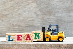 Stuk speelgoed de brievenblok n van de vorkheftruckgreep aan woordhelling op houten achtergrond stock afbeeldingen