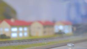 Stuk speelgoed de lay-out van de hobbyspoorweg met trein en huizen stock footage