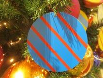 Stuk speelgoed in de vorm van een heldere blauwe cirkel met een rode streep op een Kerstboom met slinger Stock Foto's