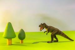 Stuk speelgoed dinosaurus in een stuk speelgoed bos zoals echt T -t-rex op een heldere studioachtergrond met houten bomen Ecospee stock afbeelding