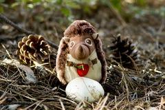 Stuk speelgoed egel in het hout als decoratie Egelstuk speelgoed dichtbij de paddestoel in een levendig bos met kegels stock fotografie
