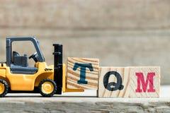 Stuk speelgoed geel de brievenblok T van de vorkheftruckgreep aan volledig woord TQM& x28; Afkorting van totale kwaliteit managem royalty-vrije stock foto