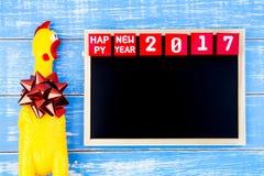 Stuk speelgoed gele kip, Bord en Gelukkig nieuw jaar 2017 aantal  Royalty-vrije Stock Foto