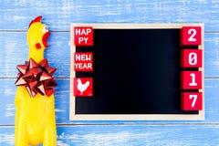 Stuk speelgoed gele kip, Bord en Gelukkig nieuw jaar 2017 aantal  Royalty-vrije Stock Afbeelding