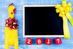 Stuk speelgoed gele kip, Bord en Gelukkig nieuw jaar 2017 aantal  Royalty-vrije Stock Afbeeldingen