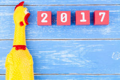 Stuk speelgoed gele shrilling kip en Gelukkig nieuw jaar 2017 aantal op r Stock Foto's