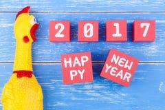 Stuk speelgoed gele shrilling kip en Gelukkig nieuw jaar 2017 aantal op r Royalty-vrije Stock Afbeeldingen