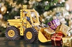 Stuk speelgoed graafwerktuig met Kerstmisgiften stock foto's