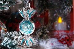 Stuk speelgoed het hangen op een tak van een Kerstboom tegen een rode lantaarn met een kaars Royalty-vrije Stock Foto