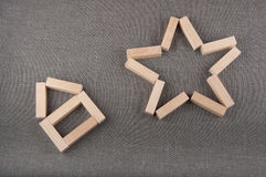 Stuk speelgoed het huis en de ster van houten blokken wordt gemaakt leggen op grijze stoffenachtergrond die Stock Afbeeldingen