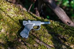 Stuk speelgoed het kanon van lood wordt gemaakt ligt op een oude boom met mos dat royalty-vrije stock afbeeldingen