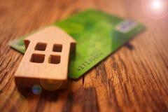 Stuk speelgoed huis, creditcard - concept leningen aan landbouwers bij rente, bedrijfs gestemd geld, stock afbeeldingen