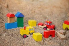 Stuk speelgoed huis en vrachtwagens van houten blokken in zandbak wordt gemaakt die Stock Afbeelding