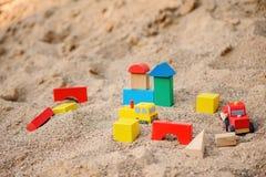 Stuk speelgoed huis en vrachtwagens van houten blokken in zandbak wordt gemaakt die Royalty-vrije Stock Foto