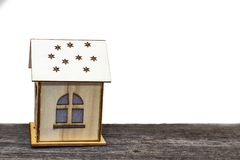 Stuk speelgoed huis met sleutels en contant geld op oude houten Raad, op wit geïsoleerde achtergrond stock foto